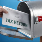 hand putting tax returns in mailbox
