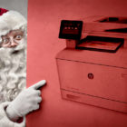 Santa Claus pointing at a printer