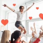 People celebrating in an office with floating hearts